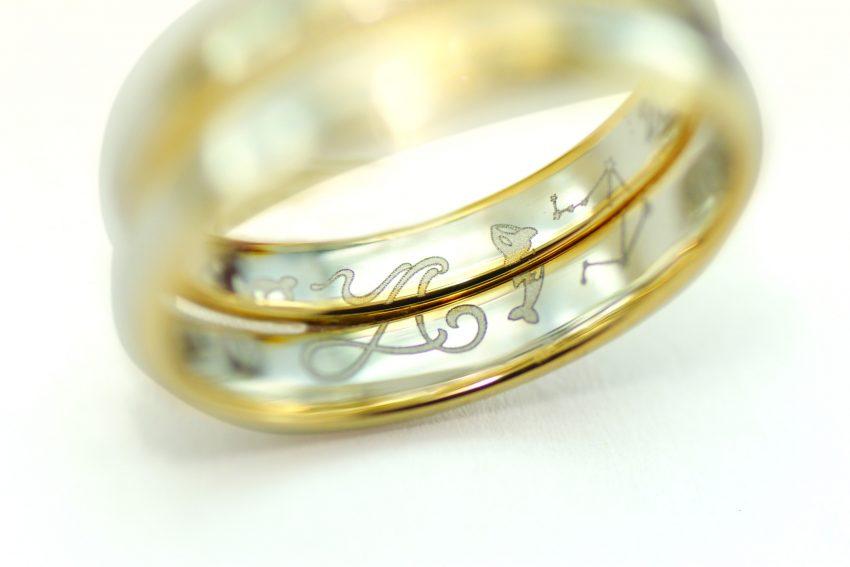 結婚指輪の内側に入れたふたりのイニシャルとシャチ、星座のイラスト